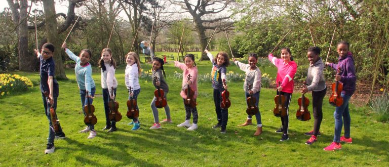 Children posing with violins in garden