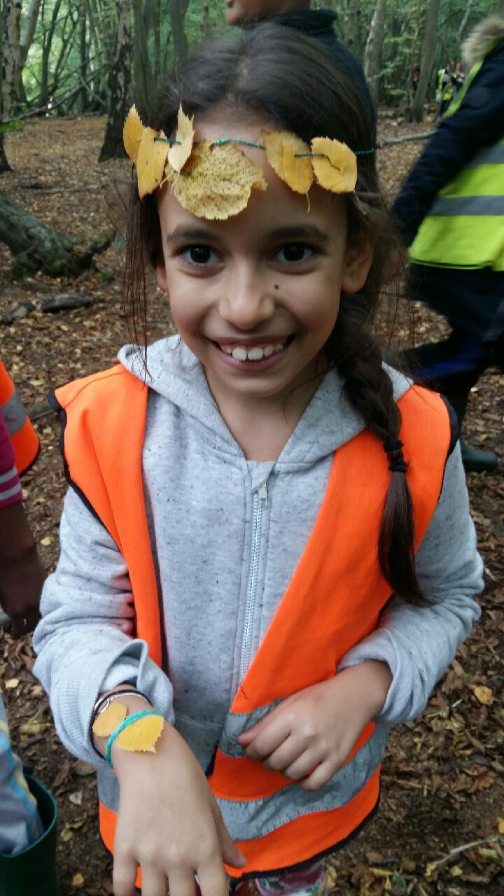 Child in hi-vis jacket with leaf crown