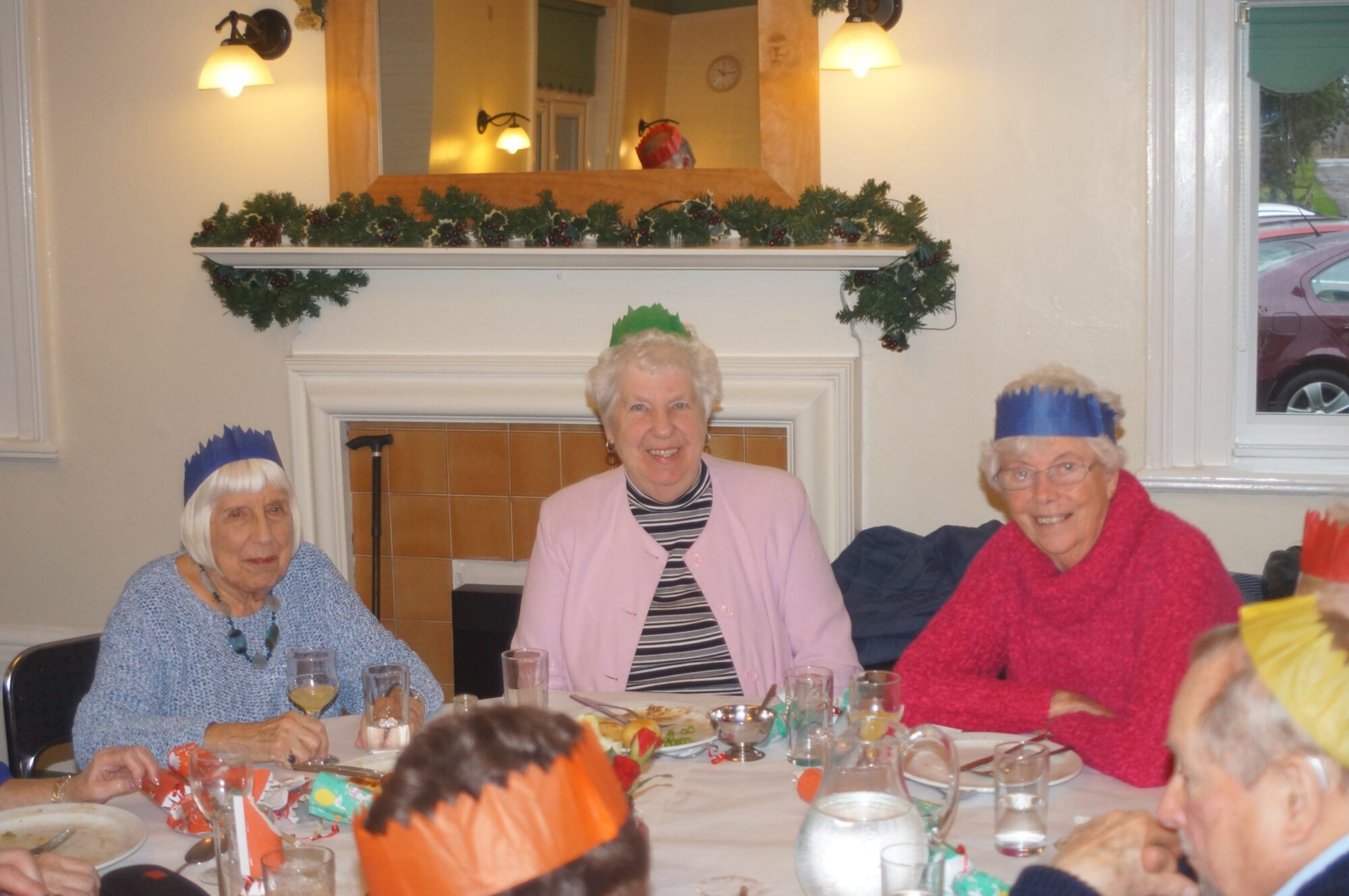 Women sat at table having Christmas lunch